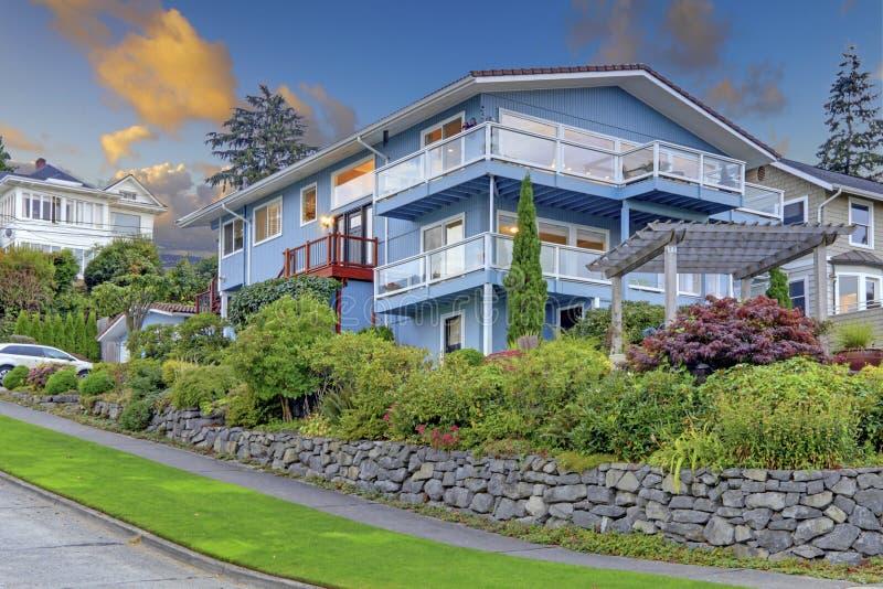Groot drie verhaal lang blauw huis met de zomerlandschap en rotsmuur stock afbeelding