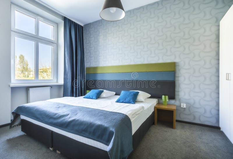 Groot eenspersoonsbed in blauwe hotelflat royalty-vrije stock afbeeldingen