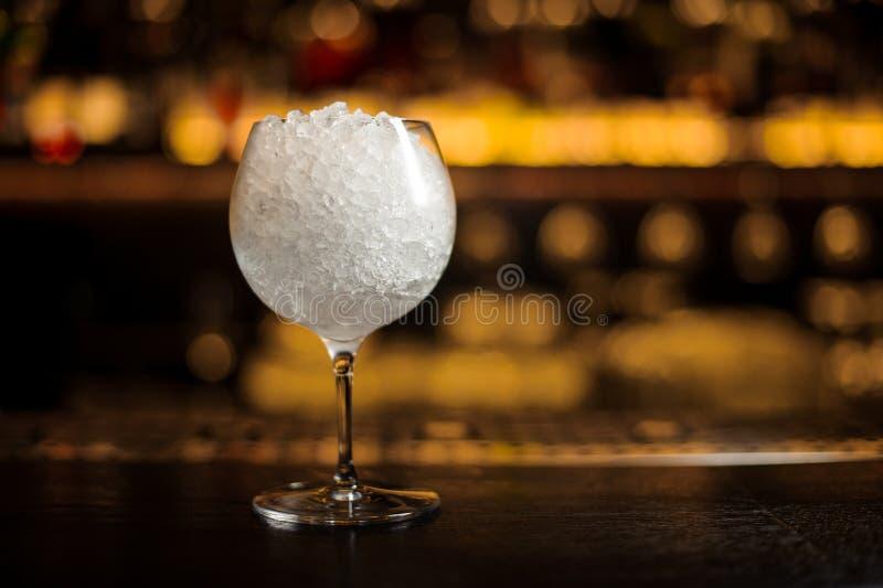 Groot elegant rond die cocktailglas met heel wat ijs wordt gevuld stock foto's