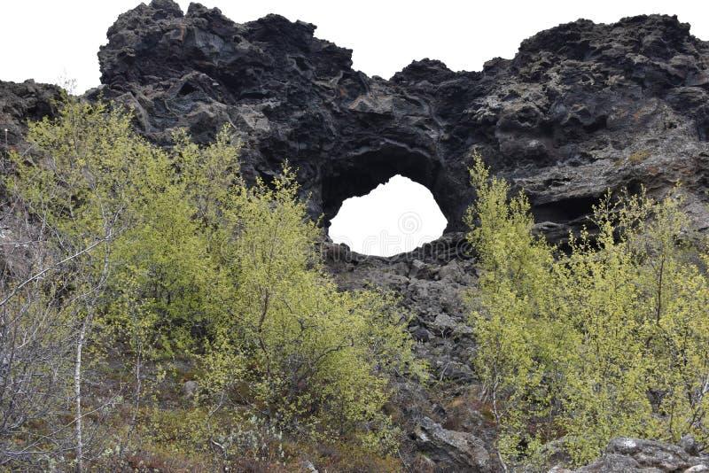 Groot gat in de rots bij lavagebied Dimmu Borgir in Myvatn, IJsland royalty-vrije stock fotografie