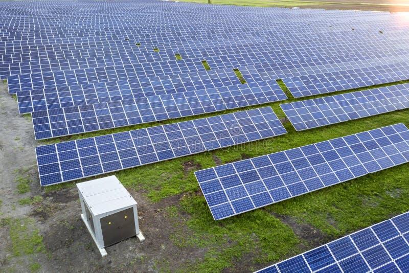 Groot gebied van het zonnesysteem die van foto voltaic panelen vernieuwbare schone energie op groene grasachtergrond veroorzaken royalty-vrije stock afbeelding