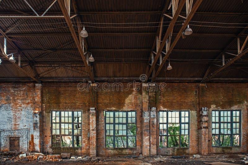 Groot gebroken venster in de verlaten geruïneerde industriële pakhuis of fabrieksbouw binnen, ruïnes en vernielingsconcept royalty-vrije stock afbeelding