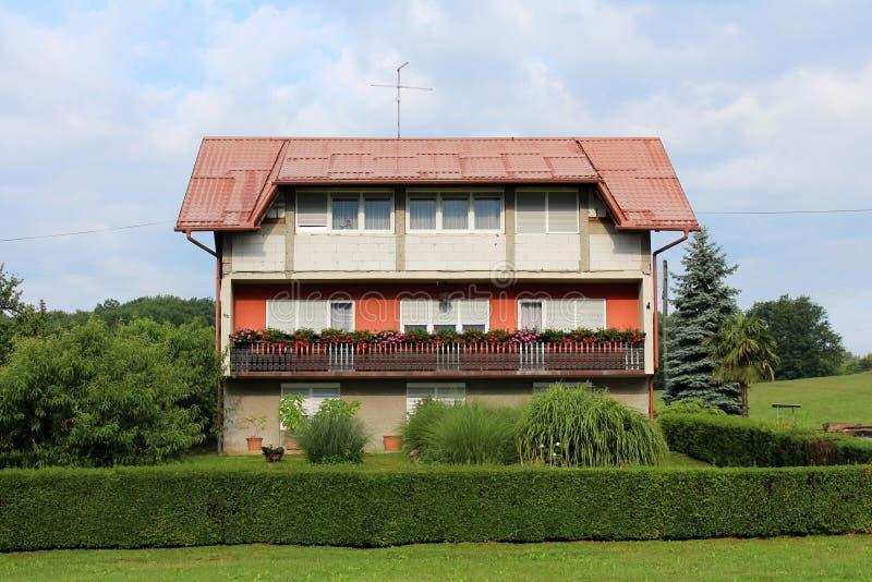 Groot gedeeltelijk onvolledig familiehuis in de voorsteden met lang die balkon met gras en bomen wordt omringd royalty-vrije stock fotografie