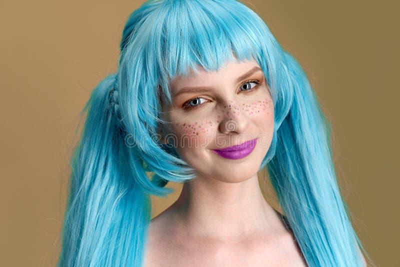 Groot gedetailleerd Studioportret van een jonge modieuze vrouw met lang blauw haar en sproeten met positieve emoties op haar gezi stock afbeelding