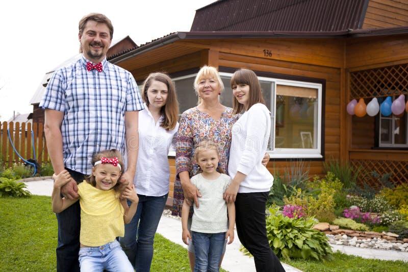 Groot gelukkig familieportret op de achtergrond van een buitenhuis stock foto's