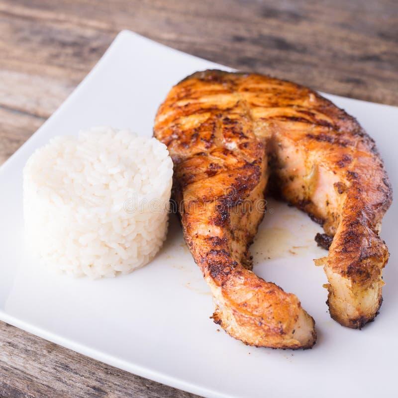 Groot geroosterd zalmlapje vlees met rijst op de plaat stock afbeelding