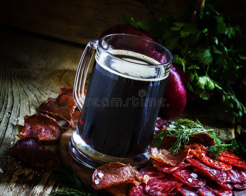 Groot glas donkere van het van de schuimbier, worst en vlees voorgerechten, donker v royalty-vrije stock fotografie
