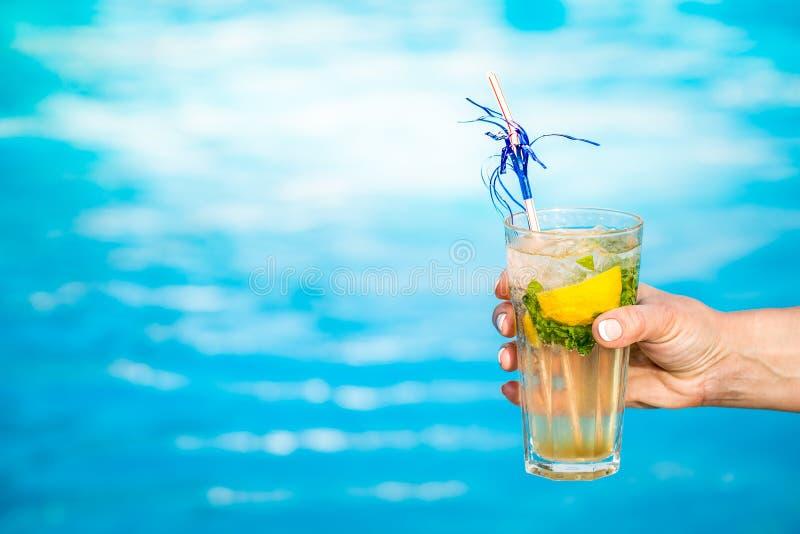 Groot glas van cocktail met munt en citroen in een meisjes` s hand tegen een blauw water van poolachtergrond royalty-vrije stock afbeeldingen
