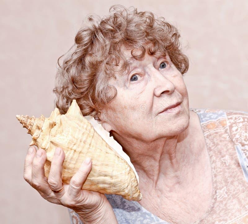 Groot glimlachen - grootmoeder het luisteren royalty-vrije stock afbeelding