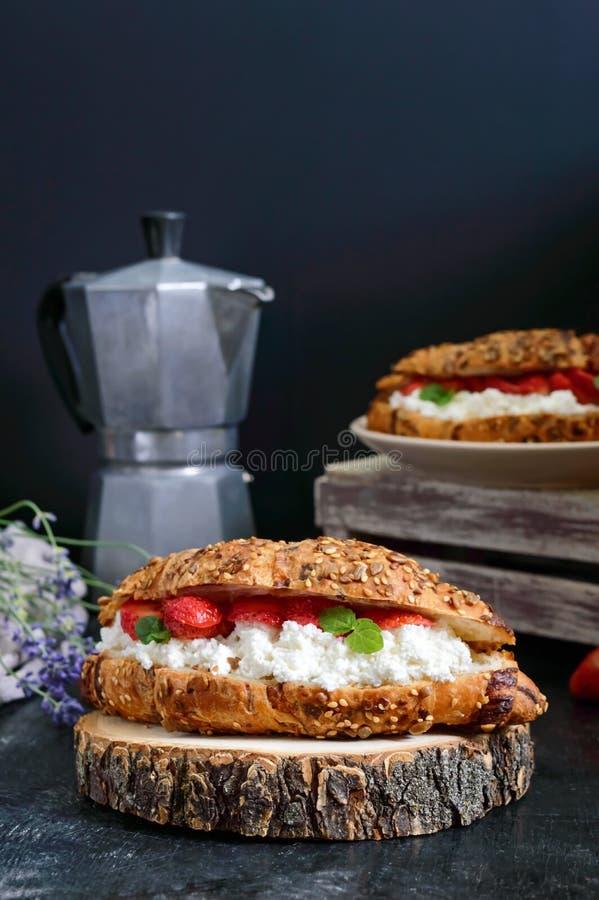 Groot graangewassencroissant met kwark en verse aardbeien op een donkere achtergrond Smakelijk Ontbijt stock fotografie