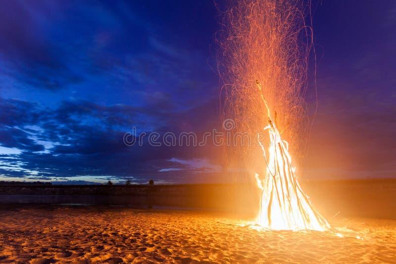 Groot helder vuur op zandig strand bij nacht royalty-vrije stock fotografie