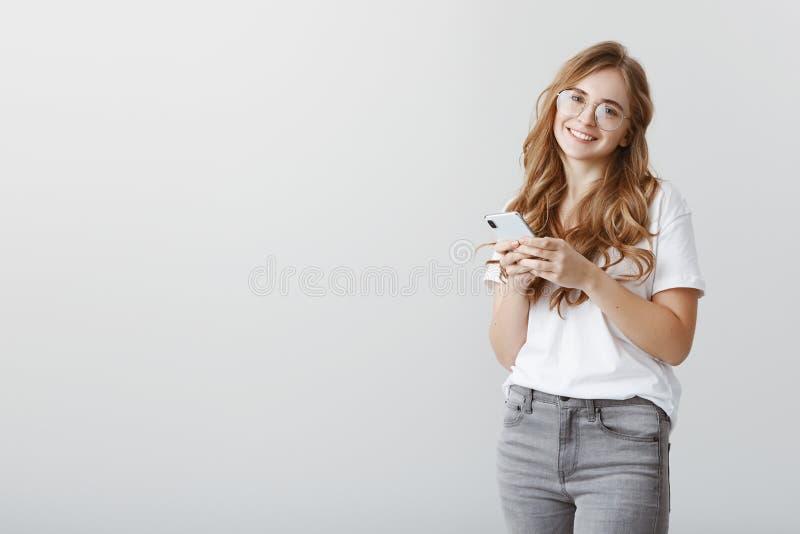 Groot het voelen in vriendencirkel Gewone gelukkige Europese vrouwelijke student in glazen en vrijetijdskleding, het houden royalty-vrije stock afbeeldingen