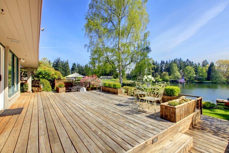 Groot houten dek met meer en de lentelandschap. stock afbeeldingen