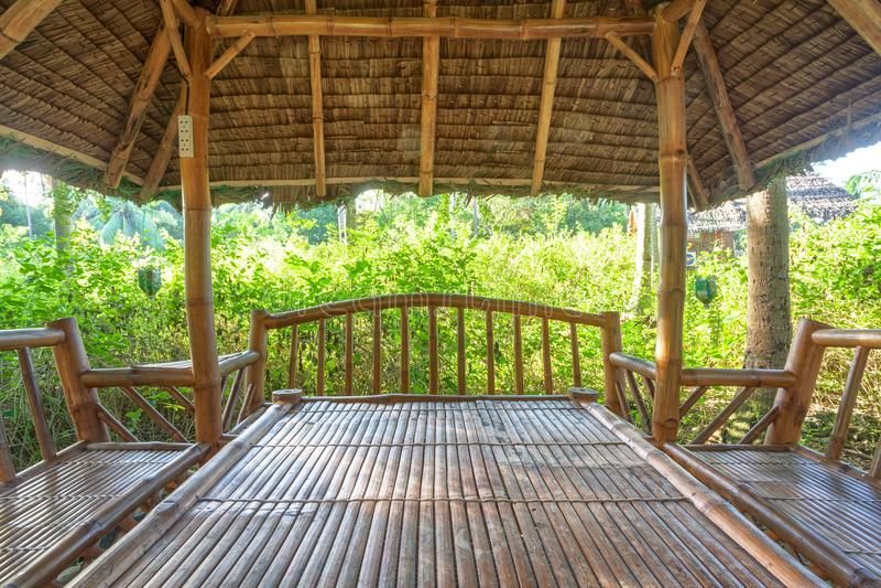 Groot houten tuinhuis met lijst en banken voor rust binnen van gazebo in aanbouw stock foto
