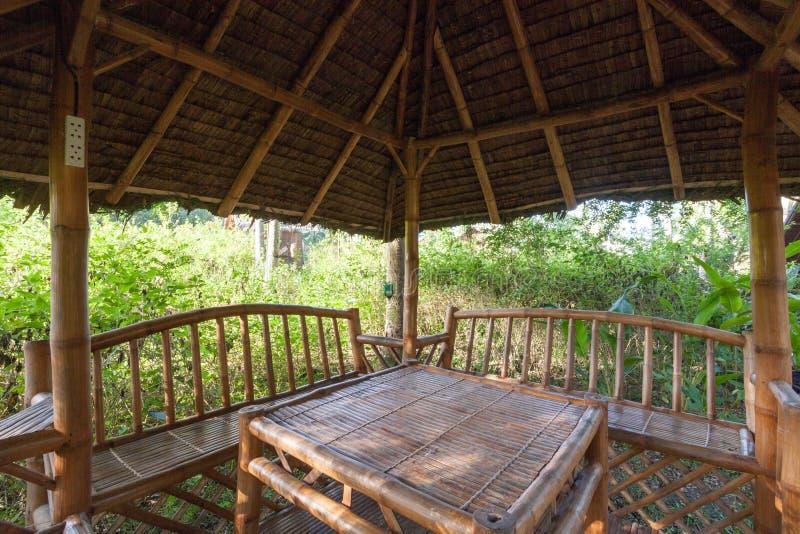 Groot houten tuinhuis met lijst en banken voor rust binnen van gazebo in aanbouw en elektrische contactdozen stock foto's