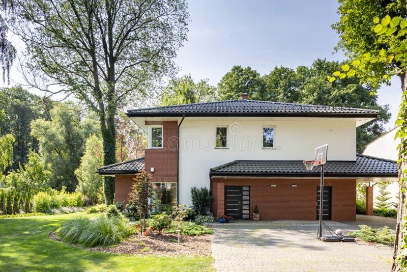 Groot huis met een mooie tuin en basketbalspeelplaats royalty-vrije stock afbeelding