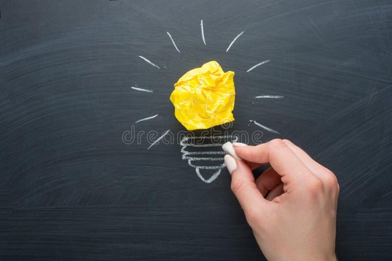 Groot ideeconcept, verfrommeld document op het bord omgezet in een gloeilamp stock afbeelding