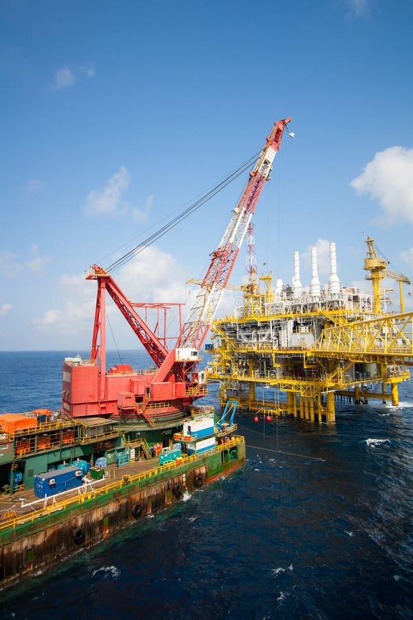 Groot kraanschip die het platform installeren in zee, kraanaak die mariene zware lift doen stock afbeeldingen