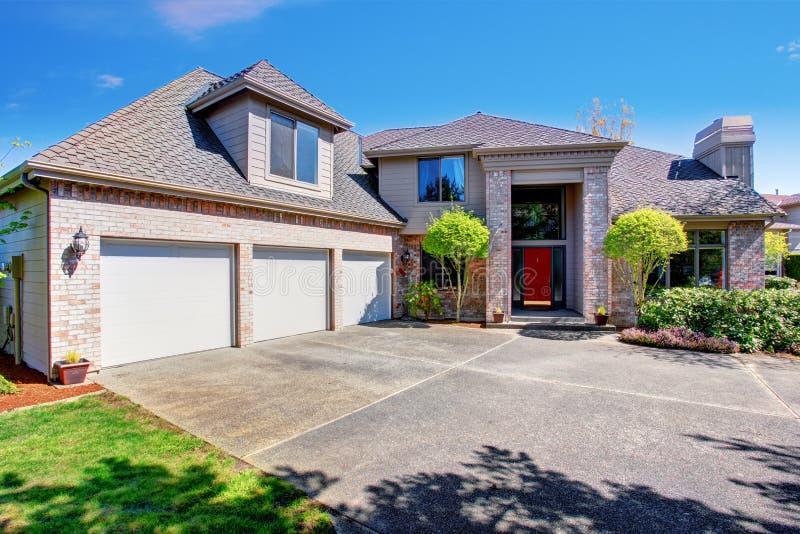 Groot modern huis met drie garageruimten en concrete oprijlaan stock foto