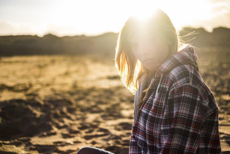 Groot mooi gouden licht in een zonsondergang met zitting van blonde de aantrekkelijke mensen molde bij het strand vakantie en rei stock afbeeldingen