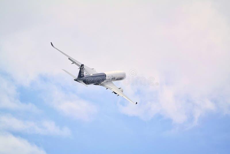 Groot Passagiersvliegtuig die onder bewolkte hemel vliegen stock afbeeldingen