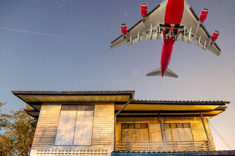 Groot passagiersvliegtuig over blokhuis in platteland stock foto