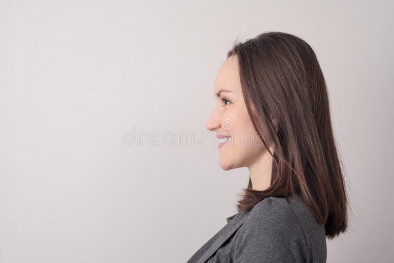 Groot portret van een het glimlachen jong brunette in profiel op een grijze achtergrond met een exemplaar van ruimte royalty-vrije stock afbeeldingen