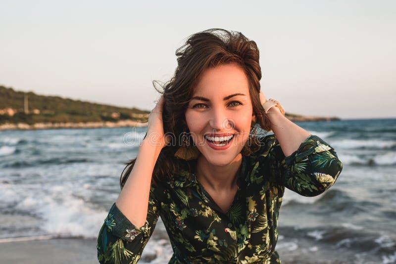 Groot portret van een jonge vrouw op het strand bij rode zonsondergang, selfie, glimlach, pret, vakantie stock foto's