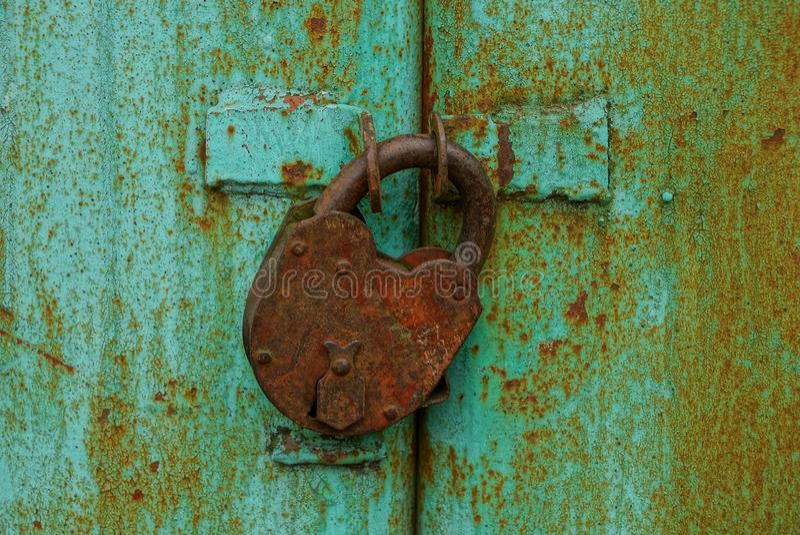 Groot roestig bruin hangslot op de ijzer groene poorten stock foto