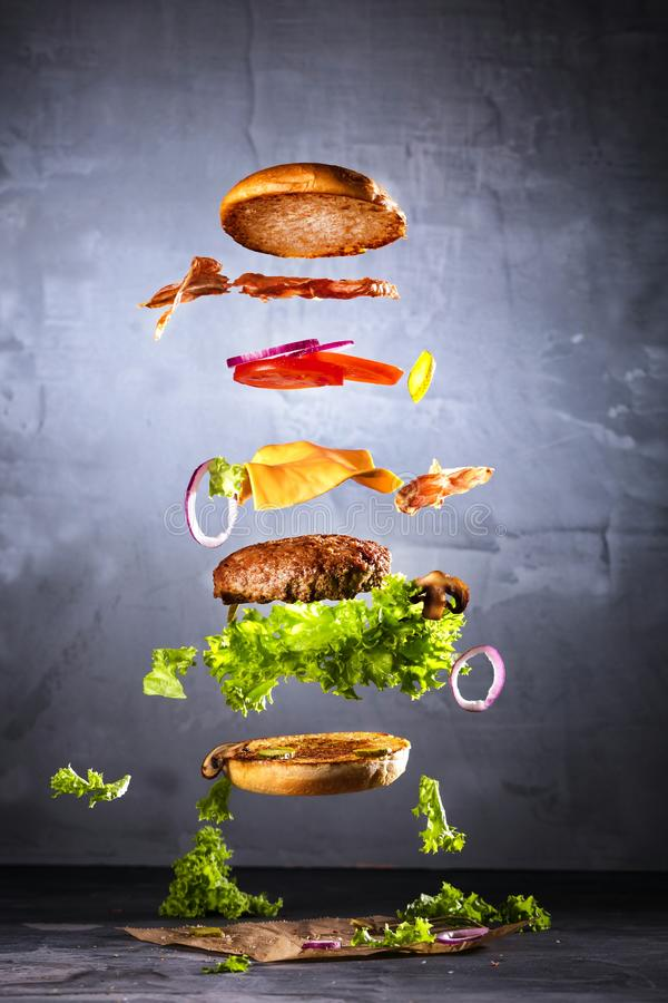 Groot smakelijk huis gemaakt tot hamburger met vliegende ingrediënten royalty-vrije stock afbeeldingen