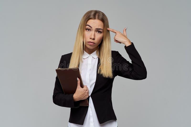 Groot Studioportret van jonge langharige bedrijfsvrouw met een dossieromslag in zijn handen met een gefrustreerde uitdrukking royalty-vrije stock foto