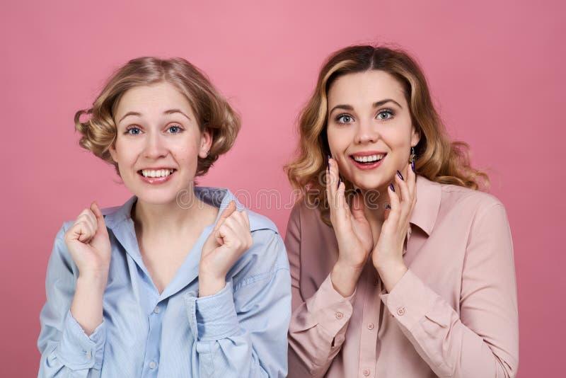 Groot Studioportret van twee jonge vrolijke meisjes in overhemden, met een brede glimlach die en enthousiast handen toejuichen ho royalty-vrije stock foto's