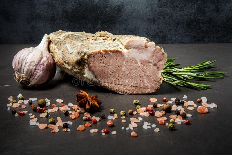 Groot stuk van gerookte gerookte ham met zout, kruiden, rozemarijn, en knoflook royalty-vrije stock foto's