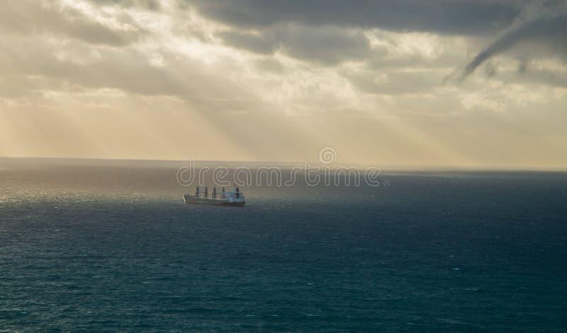 Groot tankerschip op vlotte oceaan met donkere onweerswolken in de hemel De zonnestralen worden gezien wegschietend door de wolke stock foto