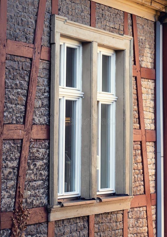 Groot venster op een oud historisch gebouw van de zandsteenvoorgevel stock fotografie