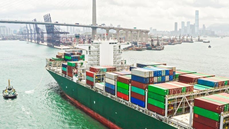 Groot vrachtschip die verzendingscontainer het aankomen Hong Kong haven, brug en stadsachtergrond, hommelsatellietbeeld vervoeren royalty-vrije stock afbeelding