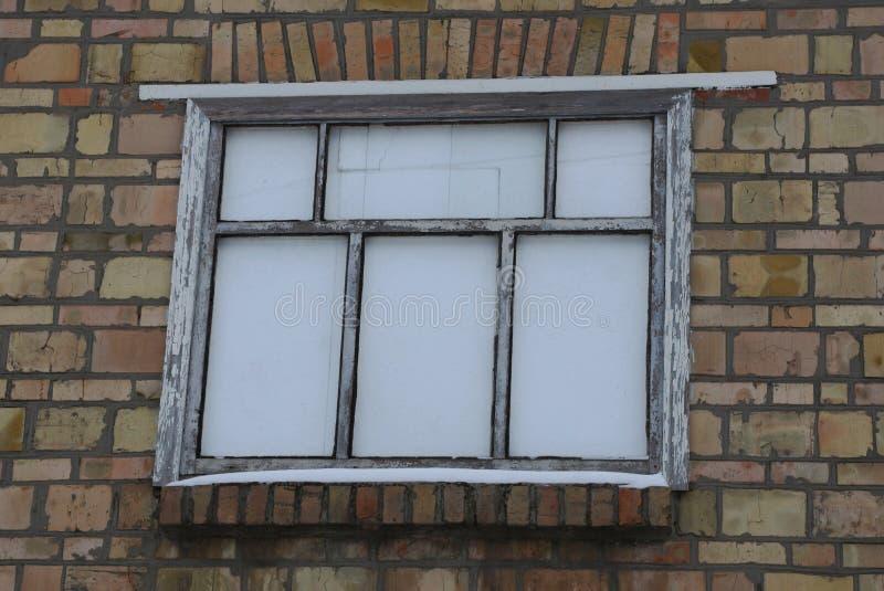 Groot wit oud venster op bruine bakstenen muur van een gebouw royalty-vrije stock foto