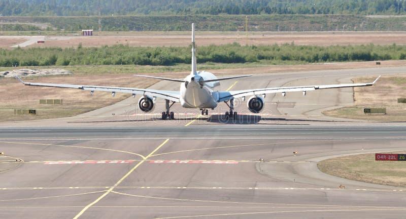 Groot wit vliegtuig op baan stock afbeeldingen