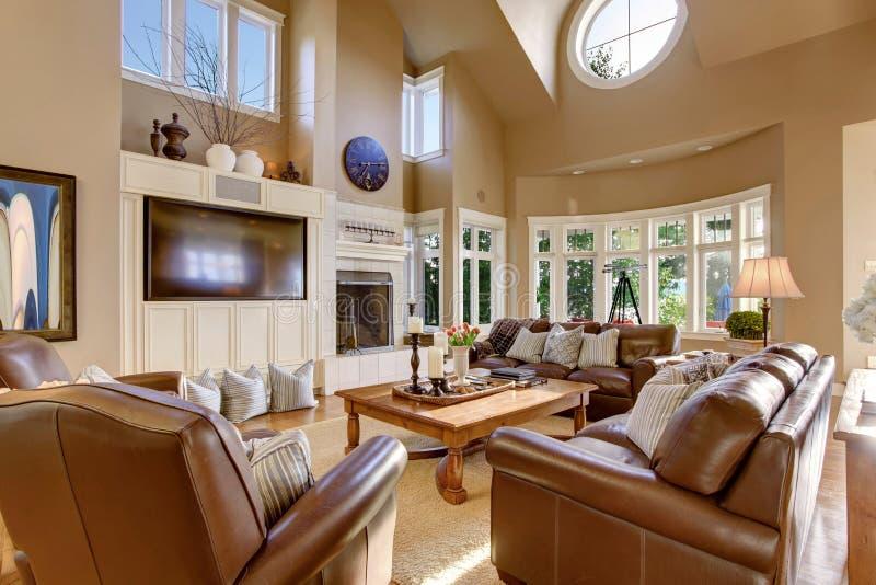 Groot woonkamer binnenlands ontwerp met hoge gewelfde plafond en leerbankreeks royalty-vrije stock foto