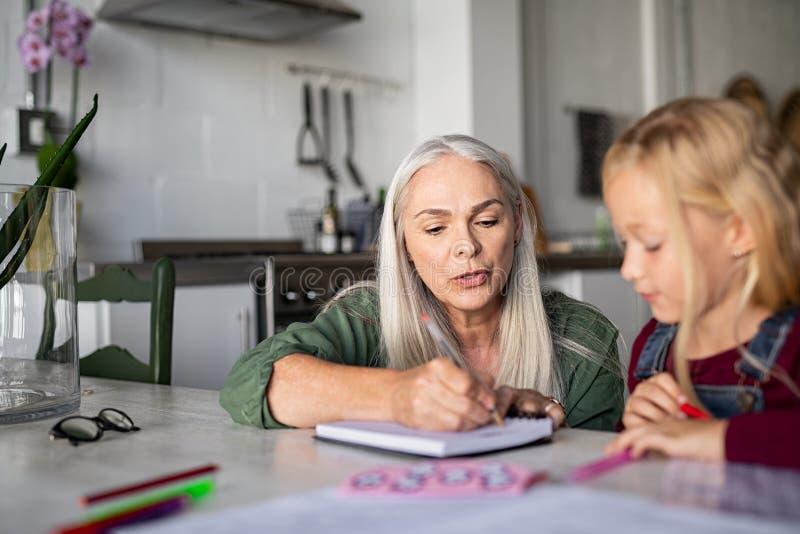 Grootmoeder die aan kleindochter thuis onderwijzen stock afbeeldingen