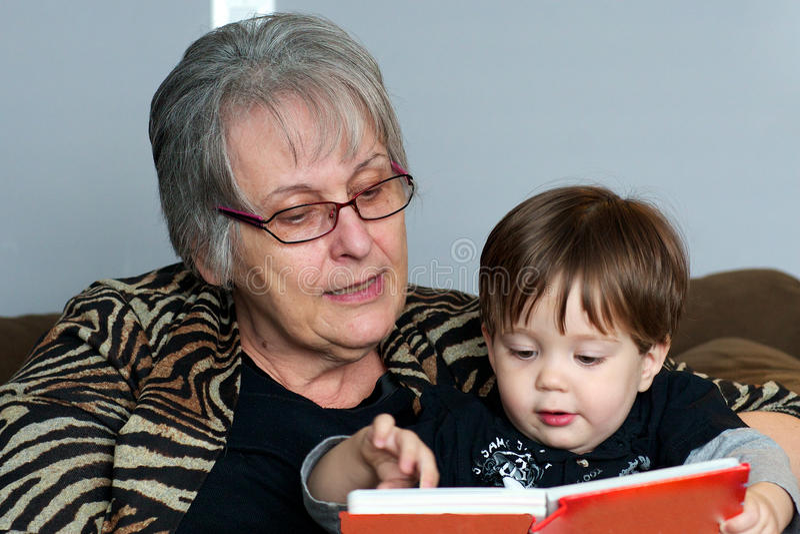 Grootmoeder die aan kleinkind leest stock afbeelding