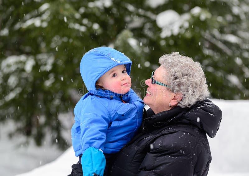 Grootmoeder die bij Kleinzoon buiten in de Winter glimlachen stock fotografie