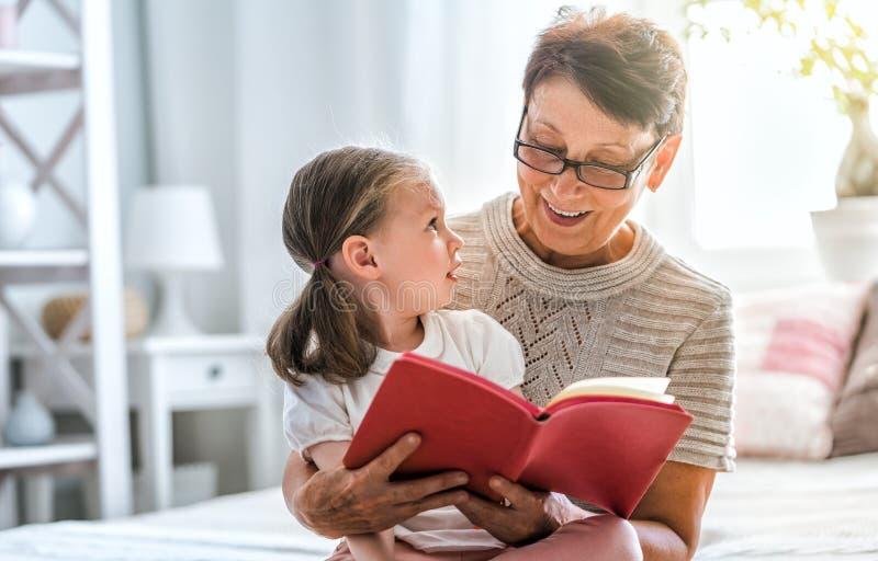 Grootmoeder die een boek leest groot zoon het luisteren toa sprookje royalty-vrije stock afbeeldingen