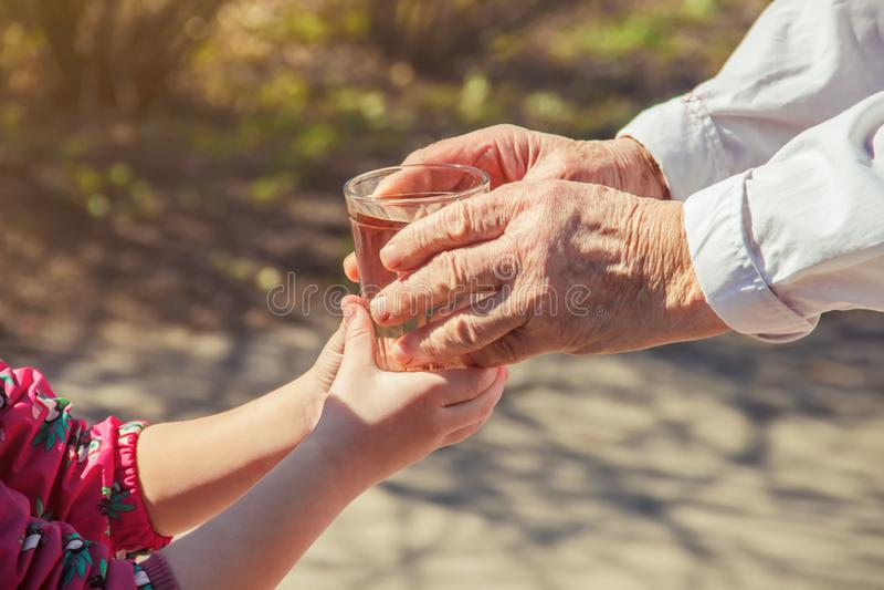 Grootmoeder die een glas schoon water geven aan een kind stock afbeelding