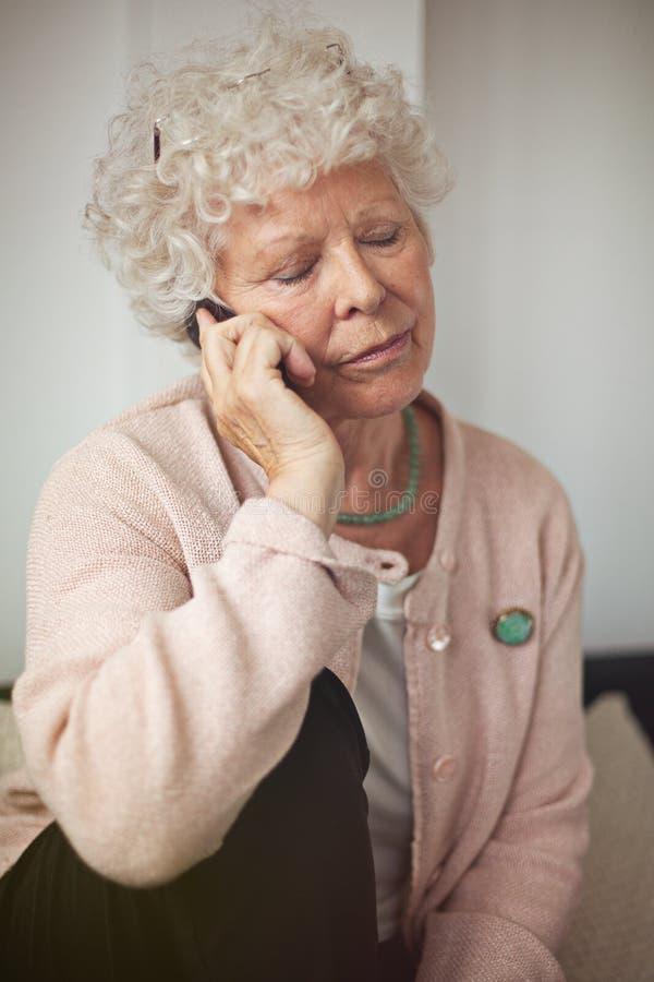 Grootmoeder Die Gebruikend Een Celtelefoon Communiceren Stock Fotografie