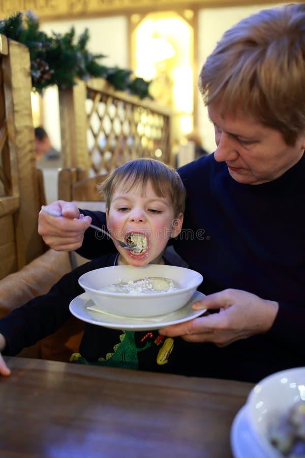 Grootmoeder die haar kleinzoon voeden stock foto