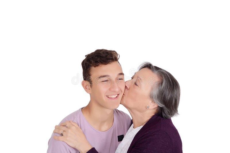 Grootmoeder die haar tienerkleinzoon kussen royalty-vrije stock foto's