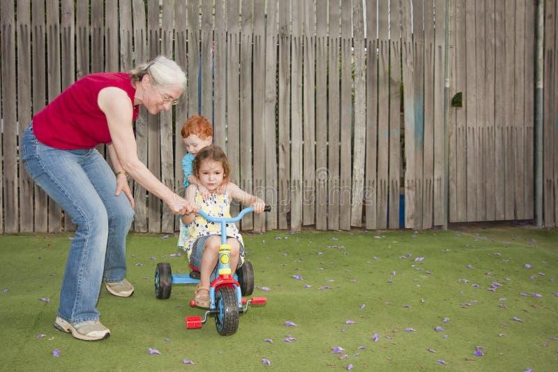 Grootmoeder die jonge geitjesrit helpt trike stock foto