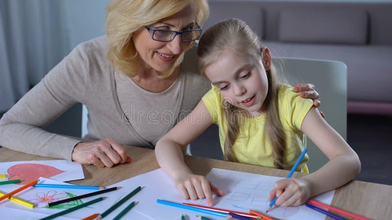 Grootmoeder die kleindochter, leuk meisje het schilderen huis met kleurpotlood koesteren stock foto