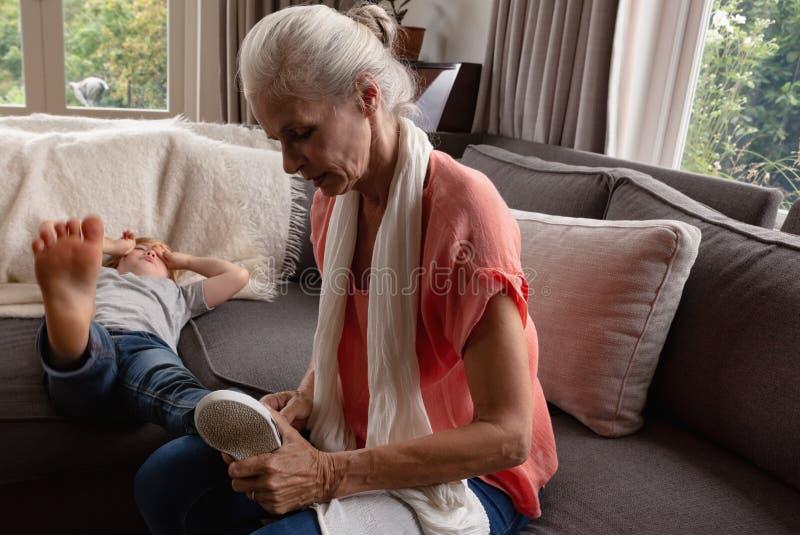 Grootmoeder die schoenen van haar kleinzoon op bank in een comfortabel huis verwijderen stock foto's